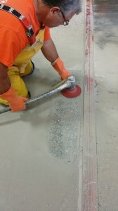This photo shows the Terrazzo Mechanic grinding the edges (border) with a terrazzo base machine.