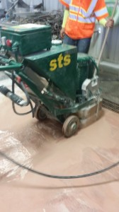 The Terrazzo Mechanic using a terrazzo floor grinding machine to grind the terrazzo floor.
